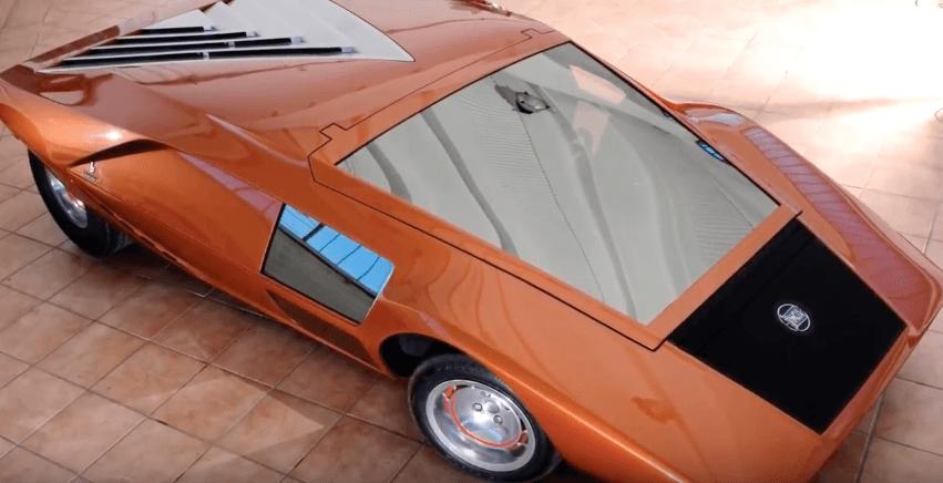 Orange 1970 Lancis Stratos HF Zero parked on tile
