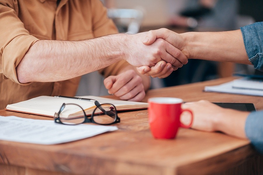 two men shaking hands over a table