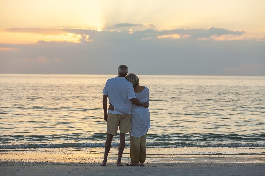 Senior man and woman couple embracing at sunset