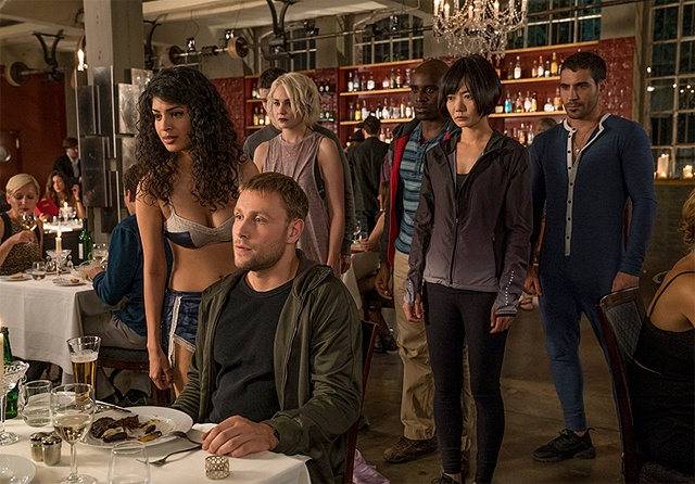 A man sits at a restaurant table while a group of characters stand behind him