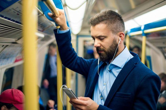 businessman with headphones travelling to work