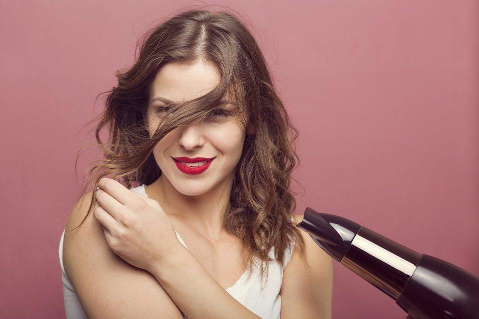 woman drying her wavy hair