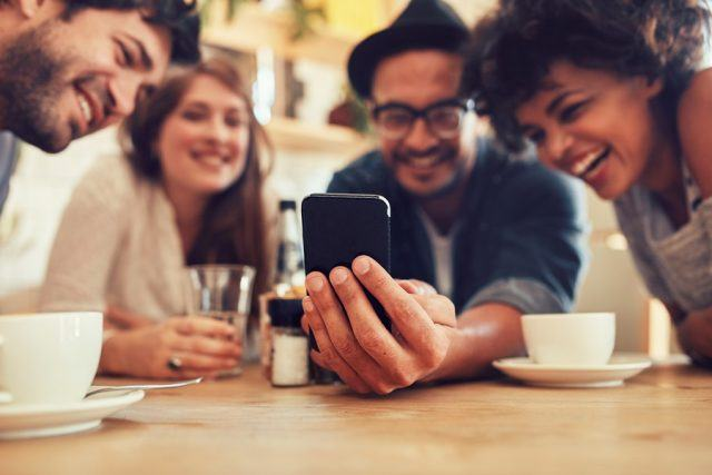 A group of friends sit at a table with a phone.