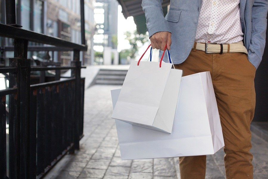 man walking on commercial street with a lot of shopping bags