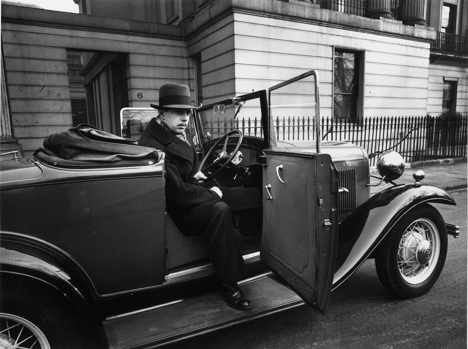 A man sitting in a Ford V8