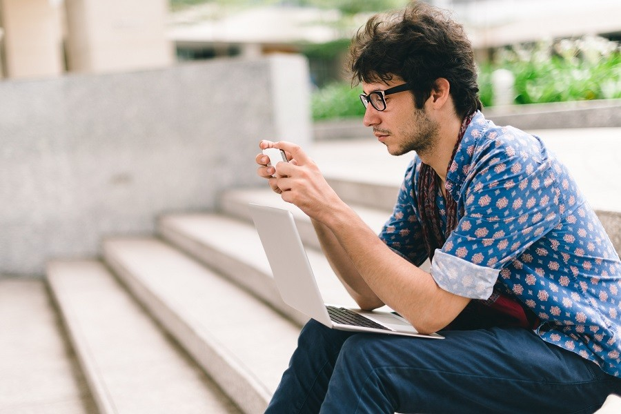 student sitting on steps and using smartphone
