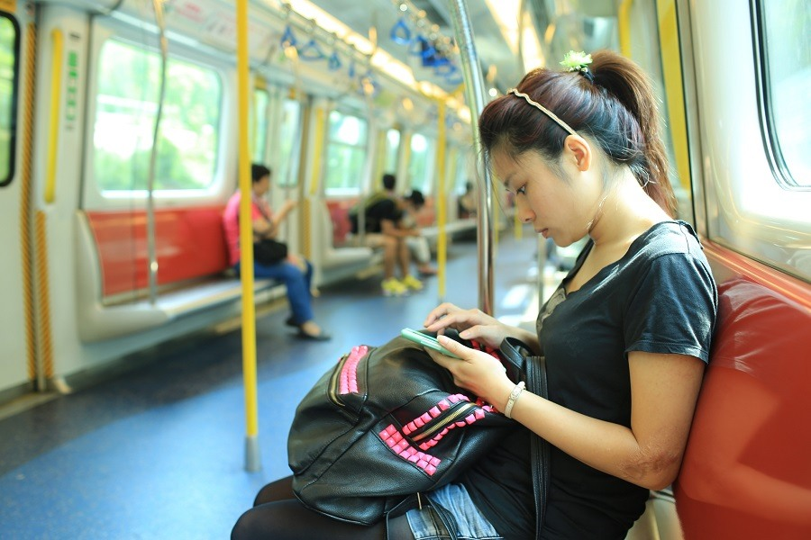 A woman checks her phone for alerts