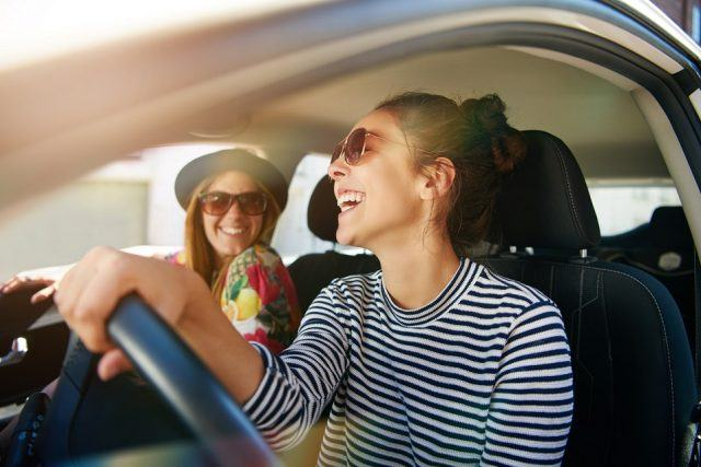 Smiling happy young woman giving her friend a lift in her car