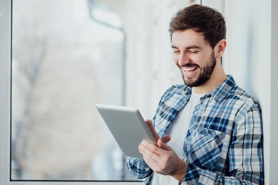 smiling man shopping with tablet pc