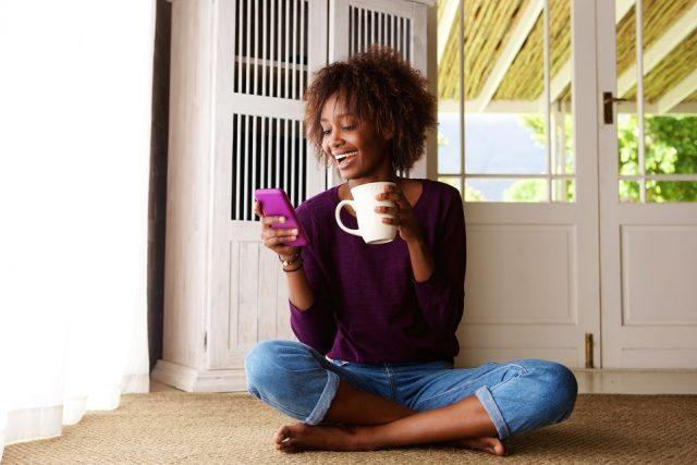 young black woman sitting on floor at home with cellphone