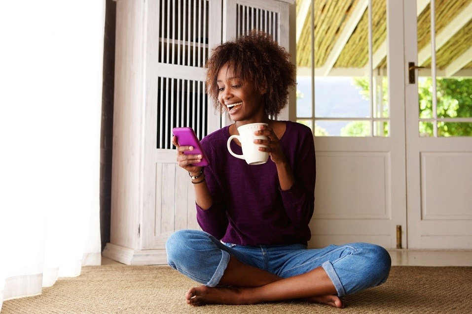young black woman sitting on floor at home with smartphone
