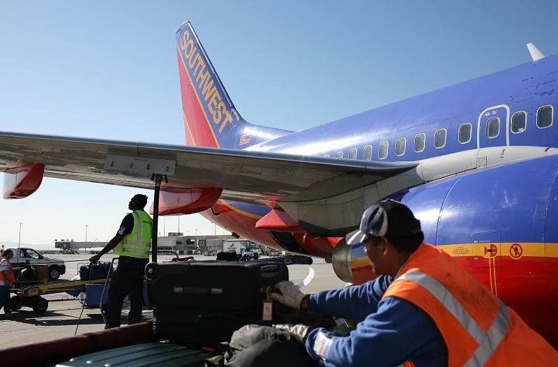 Swissport employee Omar Stewart (L) monitors a line as he fuels a Southwest Airlines plane at the Oakland International Airport October 16, 2008 in Oakland, California. Southwest Airlines reported a loss today, the first time in 17 years