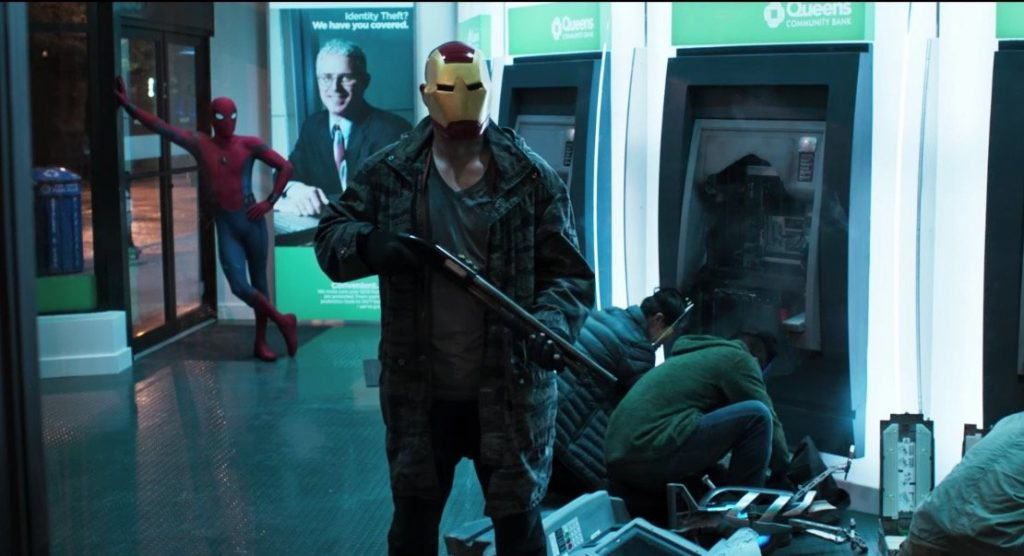 Spider-Man leans against a wall while a crew dressed as Avengers rob ATMs