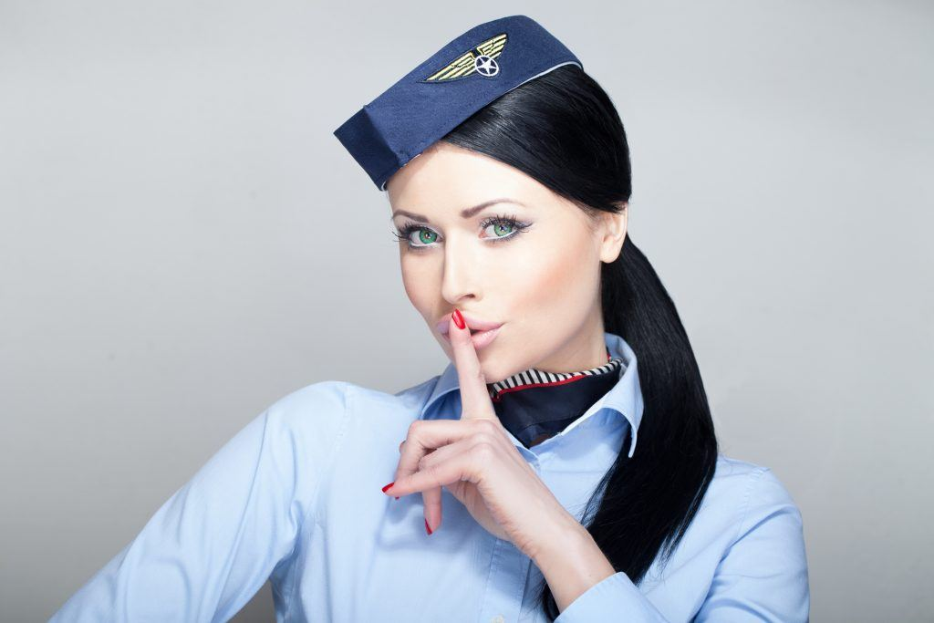 "A stewardess holds her finger to her lips, saying, ""Shh."""
