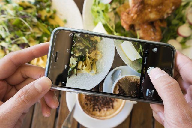 Top down view of a woman taking a photo of a meal