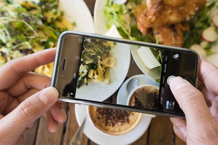 Top down view of a woman taking photo of a meal