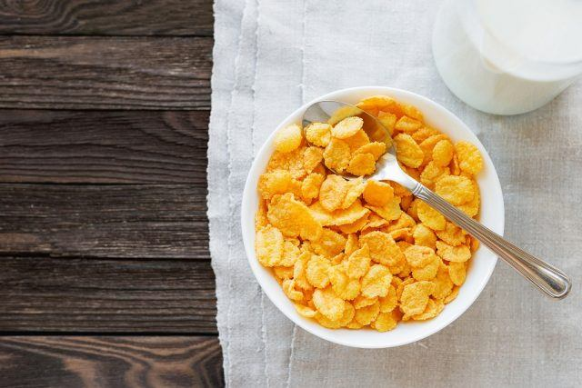 Tasty corn flakes in bowl with bottle of milk