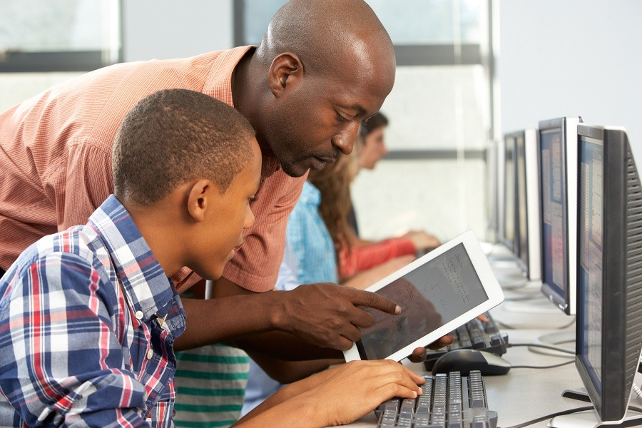 teacher helps boy use tablet