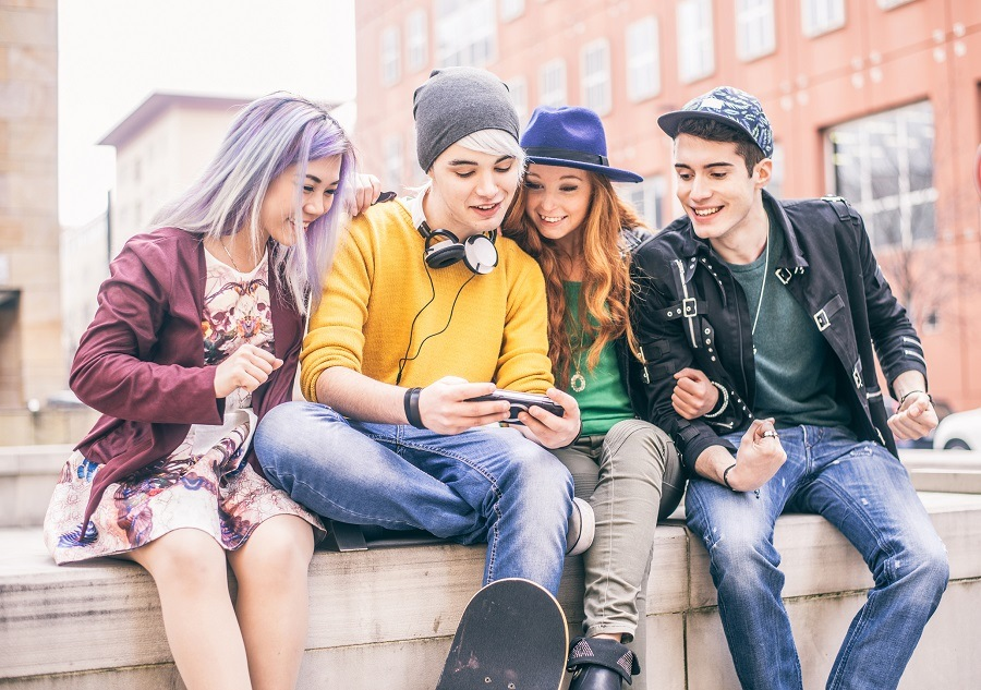 young teens playing videogames outdoors
