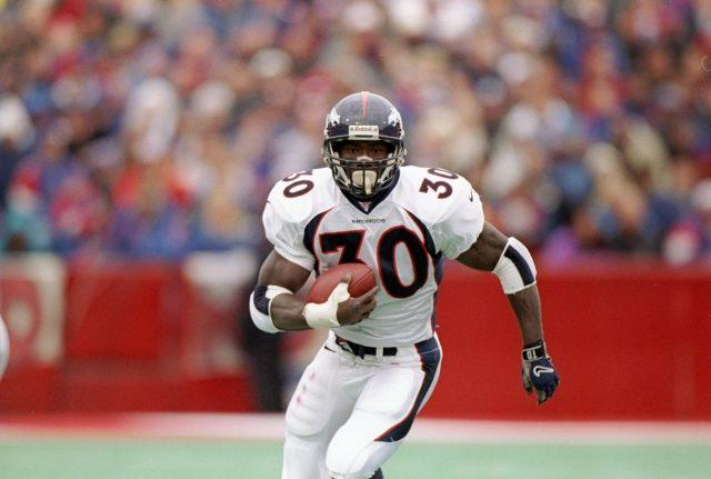 Terrell Davis running down the field with a football in hand.