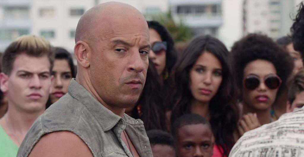 Vin Diesel in a crowd of people making a face looking to the side