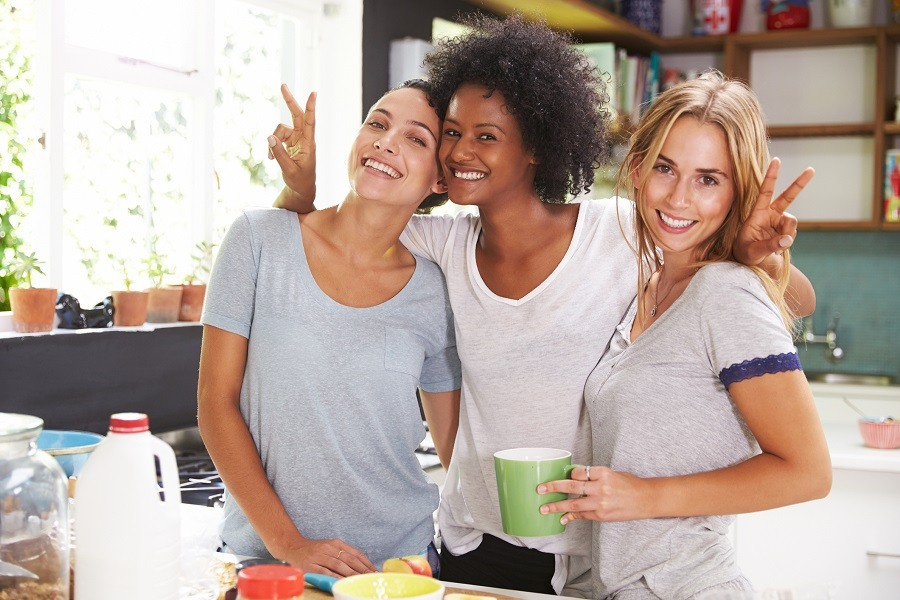Three female friends pose for a picture in the kitchen