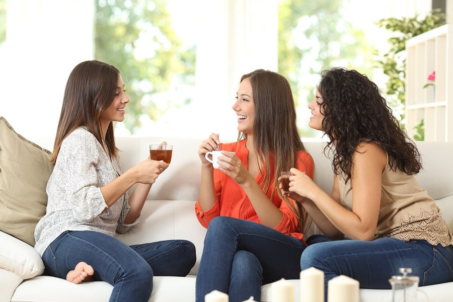 Three happy friends talking and drinking coffee
