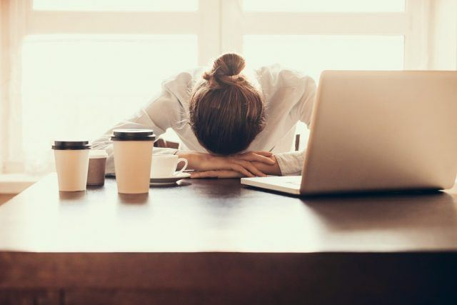 Tired businesswoman putting her head down at her desk