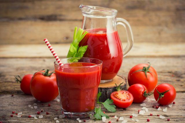 Tomato juice in glass and jug on a wooden table.