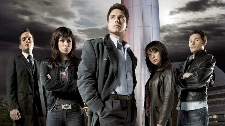 The cast of Torchwood pose under a stormy sky