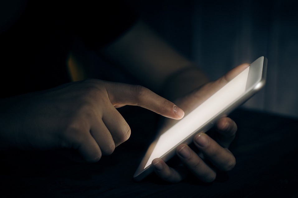 Hand touching a digital tablet