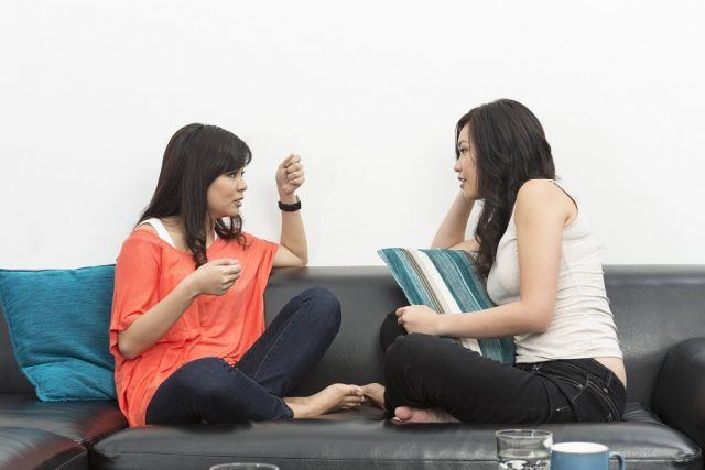 Two females having a conversation on a couch.