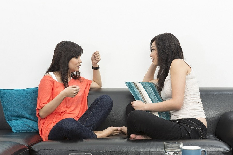 Two female Asian friends sitting on couch having conversation
