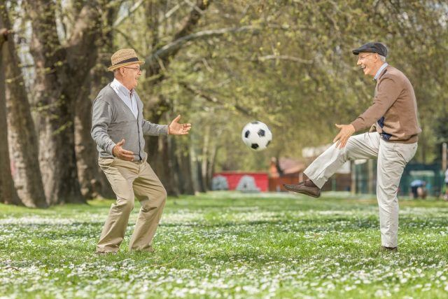 seniors playing soccer in a park