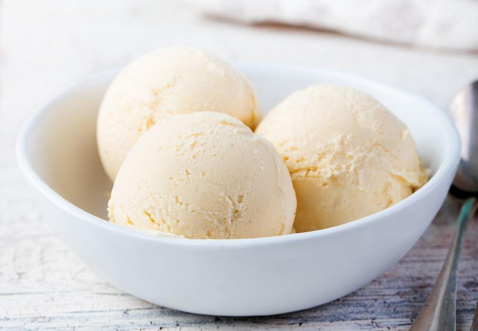 Three large scoops of vanilla ice cream in a white bowl.