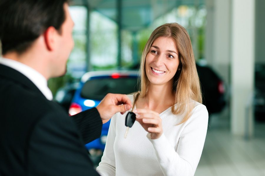Woman taking car key from car sales rep