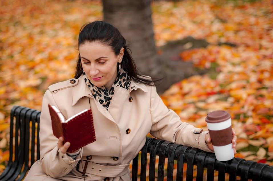 woman sitting on a bench holding a coffee and reading