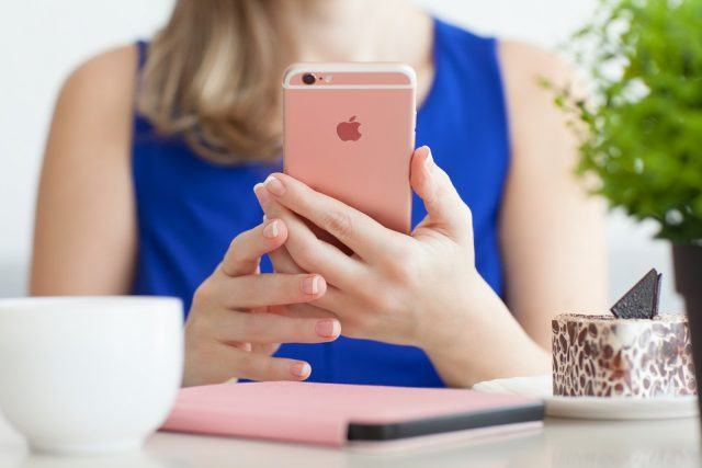 Woman holding an iPhone 6S in a cafe
