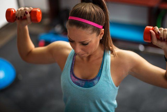 Woman lifting weights and working on her shoulders.