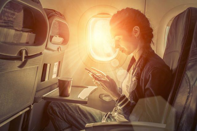 Woman uses her smartphone inside an airplane