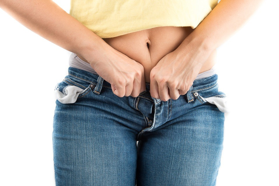 Woman trying to close jeans button
