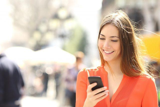 Woman wearing an orange shirt texting on a smartphone