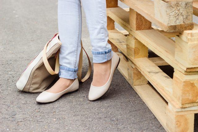 Woman's legs in jeans and white ballet flat shoes