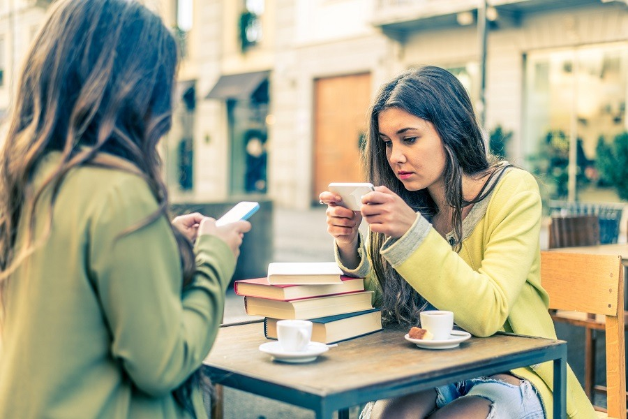 Two women sit in an outdoor cafe and stare at their mobile phones