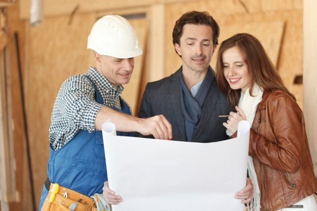 Worker shows house design plans to a couple