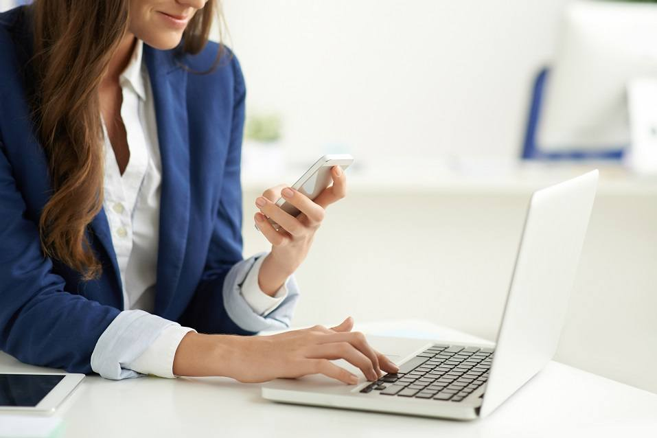 woman texting and using laptop