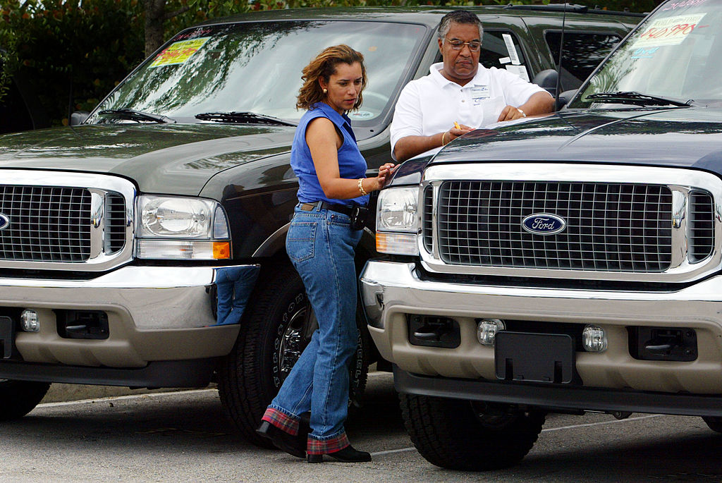 A woman looks at a new pick up truck for sale.