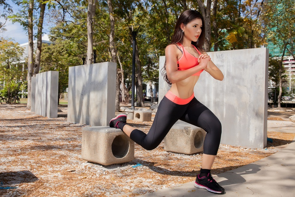 Young Asian fitness woman doing exercises in the park