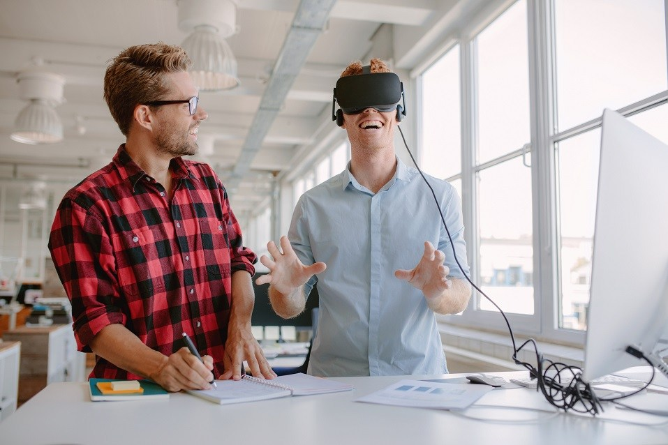 two young men testing virtual reality glasses in office