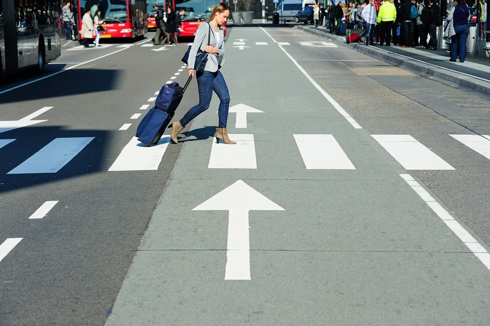 Young business traveller with carry-on bag on zebra crossing